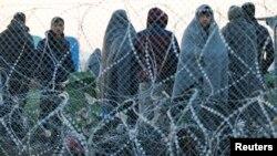Para migran yang ditolak untuk masuk ke Makedonia menunggu di Idomeni, Yunani, Selasa (23/2).