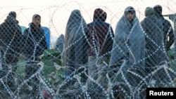 Migrants stand behind a border fence at the Greek-Macedonian border, after additional passage restrictions imposed by Macedonian authorities left hundreds of them stranded near the village of Idomeni, Greece, Feb. 23, 2016.