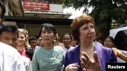 ຜູ້ນຳປະຊາທິປະໄຕມຽນມາ ທ່ານນາງອອງຊານ ຊູຈີ (ກາງ) ແລະທ່ານນາງ Catherine Ashton ຫົວໜ້ານະ ໂຍບາຍການຕ່າງປະເທດຂອງສະຫະພາບຢູໂຣບ ລຸນຫຼັງການພົບປະແລະການຖະແຫຼງຂ່າວຮ່ວມກັນ ຢູ່ຕໍ່ໜ້າສຳ ນັກງານພັກສັນນິບາດແຫ່ງຊາດເພື່ອປະຊາທິປະໄຕ ໃນນະຄອນຢ່າງກຸ້ງ (28 ເມສາ 2012)