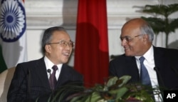 Chinese State Councilor and Special Representative on the Boundary Question, Dai Bingguo (L) and Indian National Security Adviser Shivshankar Menon smile after signing an agreement in New Delhi, India, January 17, 2012.