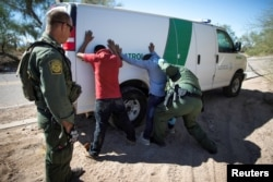 FILE - Border Patrol agents arrest migrants who crossed the U.S.-Mexico border in the desert near Ajo, Arizona, Sept. 11, 2018.