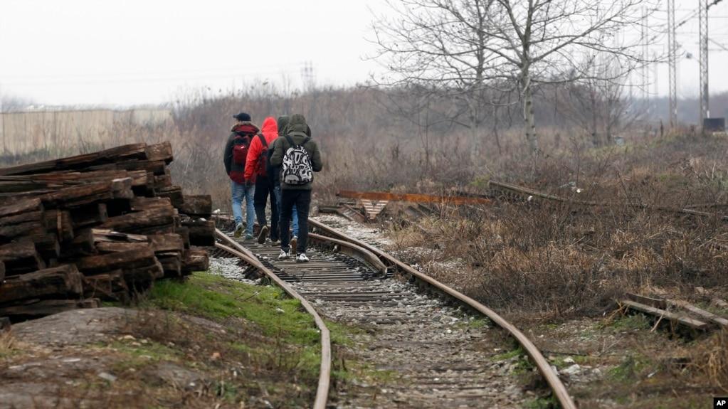 Migrants walk on train tracks near the western Serbian town of Sid, near Serbia's border with European Union member Croatia, Dec. 18, 2017.