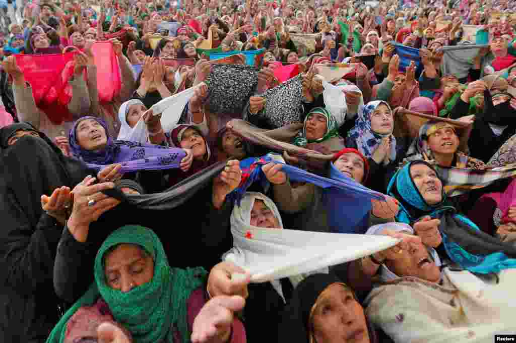 Kashmiri Muslim women pray upon seeing a relic believed to be hair from the beard of Prophet Mohammed during Meeraj-un-Nabi, at the Hazratbal shrine in Srinagar. The festival marks the rising of Prophet Mohammed to Heaven.