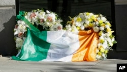 An Irish flag is draped over wreaths at the Library Gardens apartment complex in Berkeley, Calif., where six young people died in a balcony collapse, June 16, 2015.