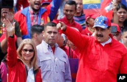 President Nicolas Maduro and first lady Cilia Flores greet supporters as they arrive at a rally in Caracas, Feb. 2, 2019.
