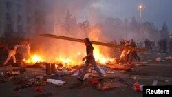 Seorang pengunjuk rasa berjalan melewati tenda separatis pr-Rusia dekat gedung Serikat Dagang yang terbakar di Odessa (2/5).