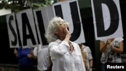 "A woman shouts slogans during a protest outside the World Health Organization (WHO) office in Caracas, Venezuela, Sept. 25, 2017. The letters read ""Health."""