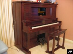 This is a player piano, also called a pianola. The piano roll, inserted into the opening, can play a tune, or the instrument can be played like a normal piano.
