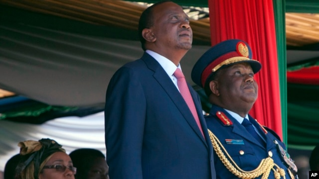 Kenyan president Uhuru Kenyatta, centre, Commander-in-Chief of the Armed Forces, left, stands with Gen Julius Waweru Karangi, right, Chief of the Defence Forces, as they watch the passing out parade and fly over by the Kenyan Air Force, Oct. 20, 2013.