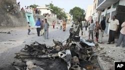 Raia wa Somalia wakiangalia gari lililolipuliwa kwa bomu katika mji mkuu Mogadishu.