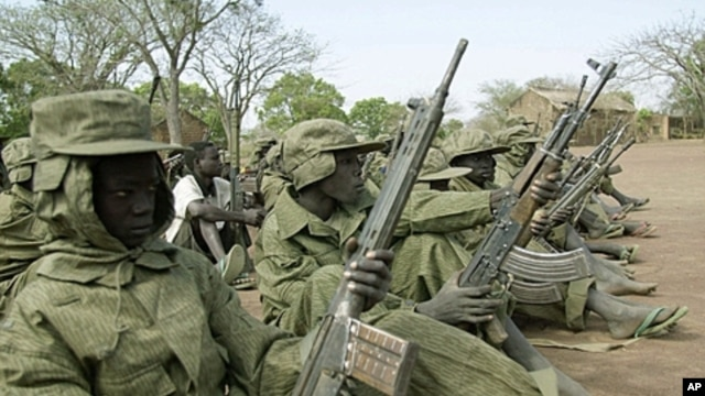 Child soldiers of the rebel Sudan People's Liberation Army (SPLA) wait for their commander at a demobilization ceremony at their barracks in Malou, southern Sudan Sunday, February 25, 2001 (file photo).