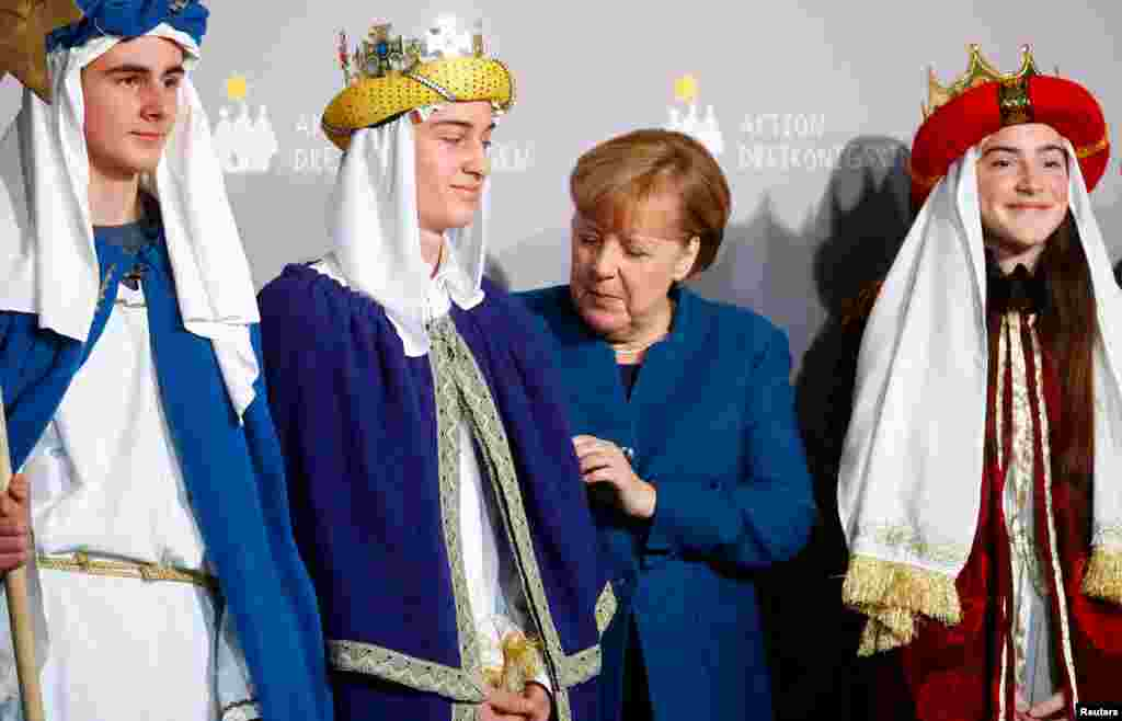 German Chancellor Angela Merkel meets carol singers during a reception at the German Chancellery in Berlin.