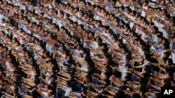 "FILE - Men and women pump their fists in the air and chant ""Defend!"" as they carry propaganda slogans calling for reunification of their country during the ""Pyongyang Mass Rally on the Day of the Struggle Against the U.S."""