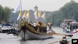 Ngọn đuốc Olympic đang được rước dọc theo sông Thames trên chiếc thuyền Gloriana của hoàng gia