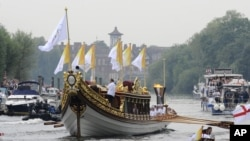 This photo provided by LOCOG shows the royal barge Gloriana carrying Olympic flame burning in the cauldron as it makes its way down the River Thames towards Richmond Bridge during the final day of the Olympic torch relay in London, July 27, 2012.