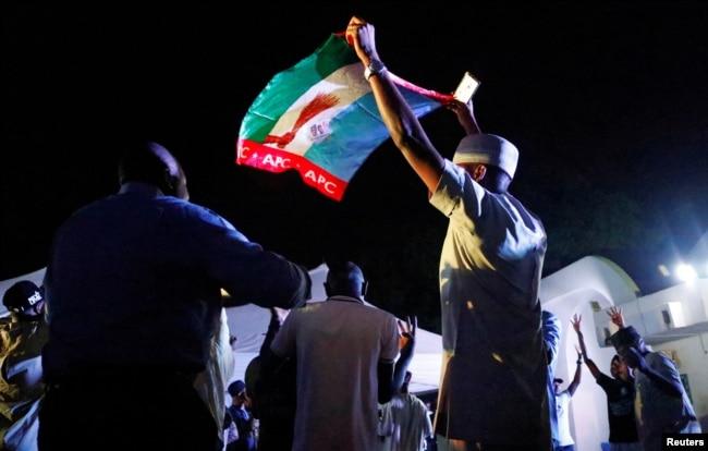 Supporters of Nigeria's President Muhammadu Buhari celebrate at the campaign headquarters of the All Progressives Congress (APC) party in Abuja, Nigeria, Feb. 26, 2019.