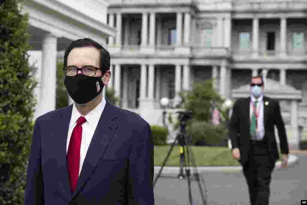 استیون منوشن وزیر خزانهداری آمریکا و یک کارمند کاخ سفید با ماسک. بعد از مشاهد مواردی از ابتلا به کرونا،زدن ماسک برای کارکنان کاخ سفید اجباری شد.