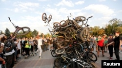 Bicycle riders place their bikes in a heap after a mass ride in Almaty, Kazakhstan.