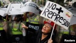 "Seorang pendukung oposisi berdiri di hadapan pasukan keamanan anti huru hara dengan memegang sebuah kertas bertuliskan ""Tidak ada penindasan lagi"" dalam sebuah aksi unjuk rasa melawan Presiden Nicolas Maduro di Caracas, Venezuela, 12 Mei 2017. ( REUTERS/Carlos Garcia Rawlin)"