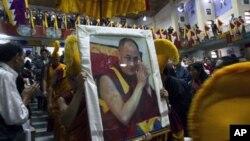 25일 인도 북부 다람살라에서 열린 티베트인 총회에서 티베트의 정신적 지도자 달라이 라마의 초상화를 들고 행진하는 참가자들.