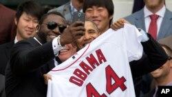 """Pemain Red Sox Boston David """"Big Papi"""" Ortiz mengambil foto """"selfie"""" bersama Presiden Barack Obama yang memegang seragam khusus untuknya."""