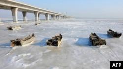 山东省青岛胶州湾大桥旁小船被冻在结冰的水面上。(2016年1月25日)