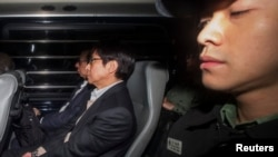 Former co-chairman of Sun Hung Kai Properties Thomas Kwok (L) and former executive director of Sun Hung Kai Properties Thomas Chan (C) sit near Correctional Services officers as they arrive at the High Court in Hong Kong, December 23, 2014.