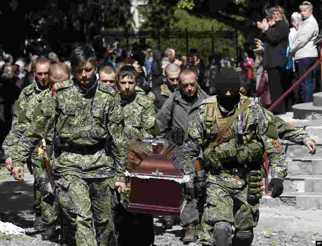 Pro-Russian gunmen carry the coffin of a person killed during last week's operation, during a commemorative service in the center of Slovyansk, eastern Ukraine, Wednesday, May 7, 2014. The U.S. and European nations have increased diplomatic efforts ahead of Ukraine's May 25 presidential election, as a pro-Russian insurgency continues to rock the country's eastern regions. (AP Photo/Darko Vojinovic)