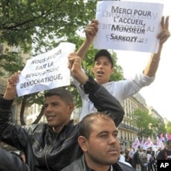 "Migrants of North African origin who hold temporary travel documents issued by Italy take part in the the annual May Day march in Paris, May 1, 2011. The posters read "" we did the democratic revolution"", ""thanks for the welcome mister Sarkozy""."
