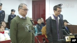 This image taken from video released on Nov. 28, 2017, by the Intermediate People's Court of Yueyang, Taiwanese activist Lee Ming-che, left, and his fellow defendant Peng Yuhua of China stand during a court session in Yueyang, Nov. 28, 2017.