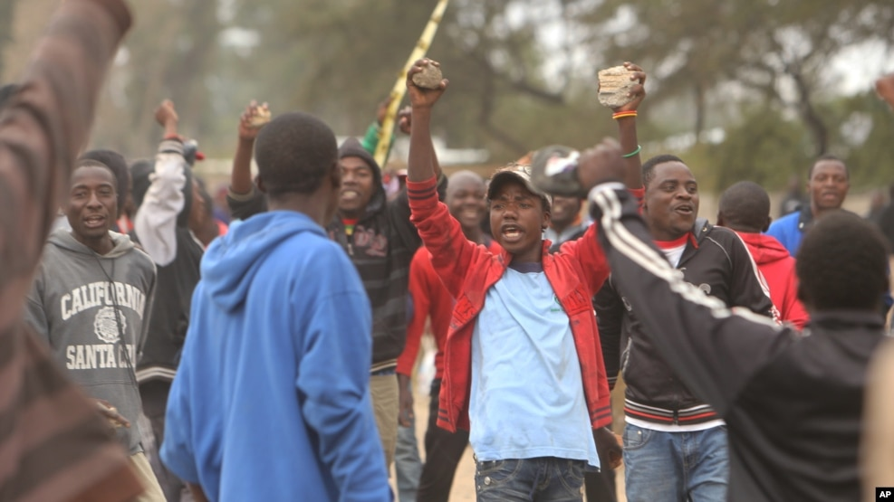 FILE - Protesters clash with Zimbabwean police in Harare, July, 4, 2016.