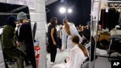 FILE - In this March 8 2015 file photo, models wait backstage during the Paris Fashion Week in Paris. Two of France's biggest luxury companies LVMH and Kering have joined forces to ban size zero models. (AP Photo/Zacharie Scheurer)