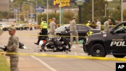 A damaged police motorcycle rests in the intersection after a vehicle crashed into a crowd of spectators during the Oklahoma State University homecoming parade, causing multiple injuries, on Saturday, Oct. 24, 2015 in Stillwater, Oklahoma.