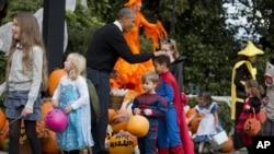 ປະທານາທິບໍດີ Barack Obama ກຳລັງຢາຍເຂົ້າໜົມ ໃຫ້ແກ່ ເດັກນ້ອຍຄົນນຶ່ງ ທີ່ນຸ່ງເຄື່ອງເປັນ Superman.