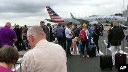 Dalam gambar ini diambil dari video ini, para penumpang berdiri di aspal landasan pacu bandara Manchester, Inggris, setelah dievakuasi, Rabu 5 Juli 2017. Pihak berwenang tengah memeriksa tas sebuah yang mencurigakan di Terminal 3 bandara tersebut.