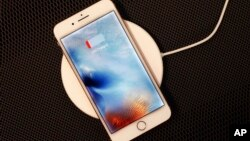 In this Sept. 15, 2017, photo, the iPhone 8 Plus rests on a wireless charger in New York. (AP Photo/Mark Lennihan)