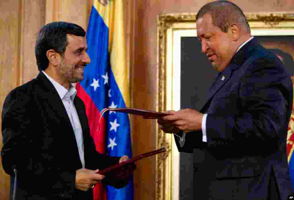 Mr. Ahmadinejad and Mr. Chavez hold up documents after signing agreements at Miraflores presidential palace in Caracas, Venezuela, on January 9, 2012. (AP)