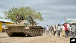 FILE - In this photo provided by the African Union Mission to Somalia (AMISOM), African Union (AU) soldiers from Uganda sit on their tank as residents walk past in the town of Bulomarer, in the Lower Shabelle region of Somalia, Aug. 31, 2014.