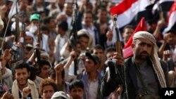 14일 예멘 사나에서 시아파 후티 반군이 무기를 들고 사우디아라비아의 공습에 항의하는 거리행진을 하고 있다.