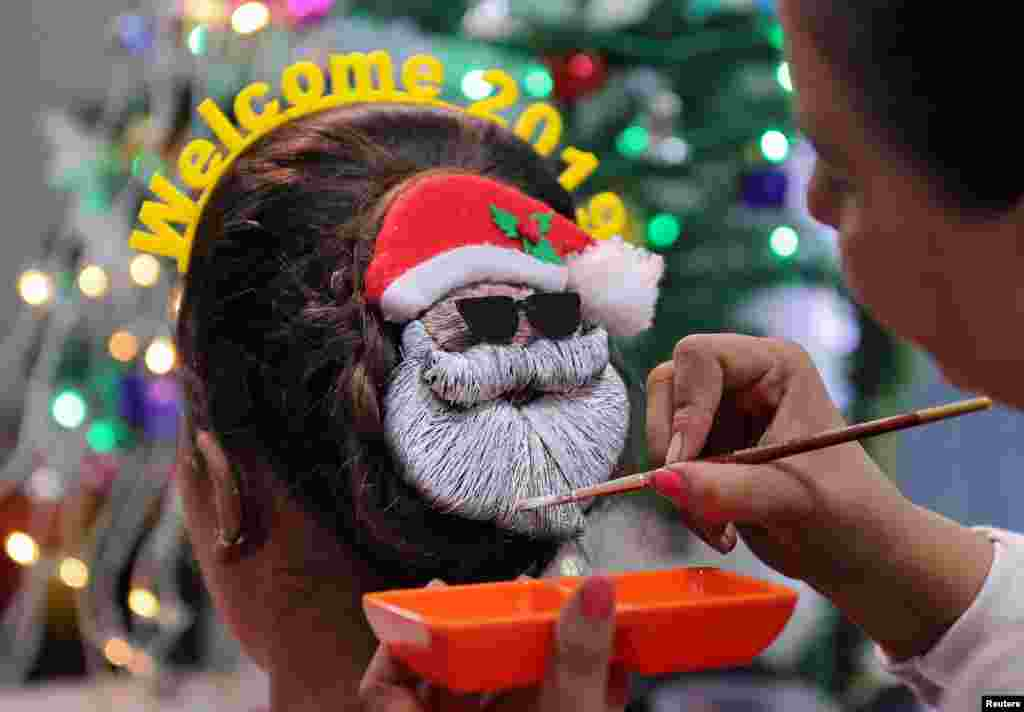 A make-up artist decorates the hair of a woman in the shape of Santa Claus during the New Year preparations in Ahmedabad, India, Dec. 31, 2018.