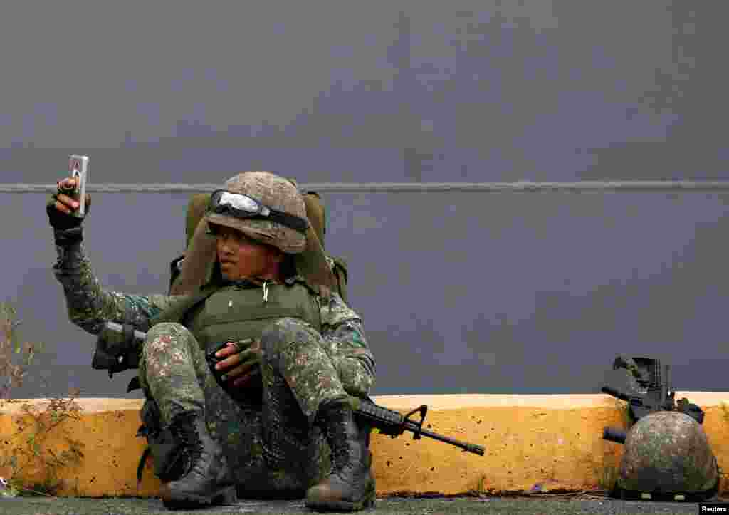A Philippine marine soldier takes a selfie with his phone during their arrival from Marawi at port area in metro Manila, Philippines.