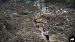 Regu penolong berupaya melakukan pencarian korban tanah longsor di desa Cililin, Jawa Barat, 25 Maret 2013. (AP Photo)