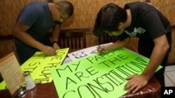 Dos jóvenes preparan en Miami carteles para una marcha en reclamo de la reforma de inmigración.