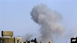 Smoke rises from an area in southeast Tripoli, Libya, April 14, 2011