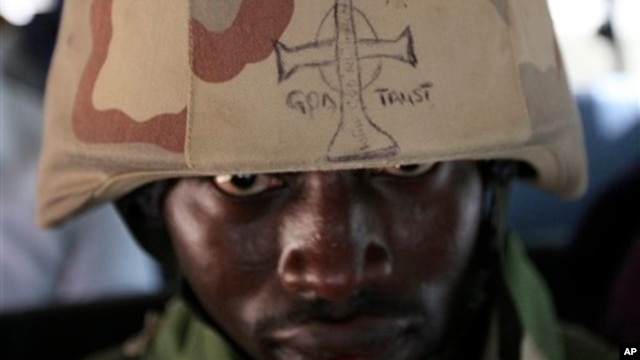 A soldier looks out from under the brim of his helmet in Maiduguri, Nigeria, June 6, 2013.