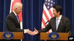 El vicepresidente Joe Biden extiende la mano al primer ministro japonés, Shinzo Abe al final de la conferencia de prensa conjunta en Tokio.