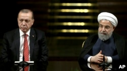 Iranian President Hassan Rouhani, right, speaks to the media during a joint press conference with Turkish President Recep Tayyip Erdogan after their meeting at the Saadabad Palace in Tehran, Iran, Oct. 4, 2017