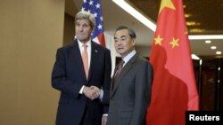 U.S. Secretary of State John Kerry, left, and Chinese Foreign Minister Wang Yi shake hands before their bilateral meeting at the Ministry of Foreign Affairs in Beijing, Jan. 27, 2016.