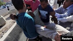 People carry a man who was injured when Libyan militiamen opened fire into a crowd of protesters in Tripoli, Nov. 15, 2013.