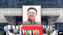 지난 21일 평양 하나음악정보센터에 걸린 김정일 위원장의 대형 영정 앞에서 주민들이 조의를 표하고 있다.
